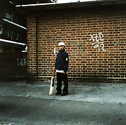 Asian boy on an holding a cricket bat looking lonely, standing in front of a brick wall with graffiti: XTC 92, East London housing estate, 1990's