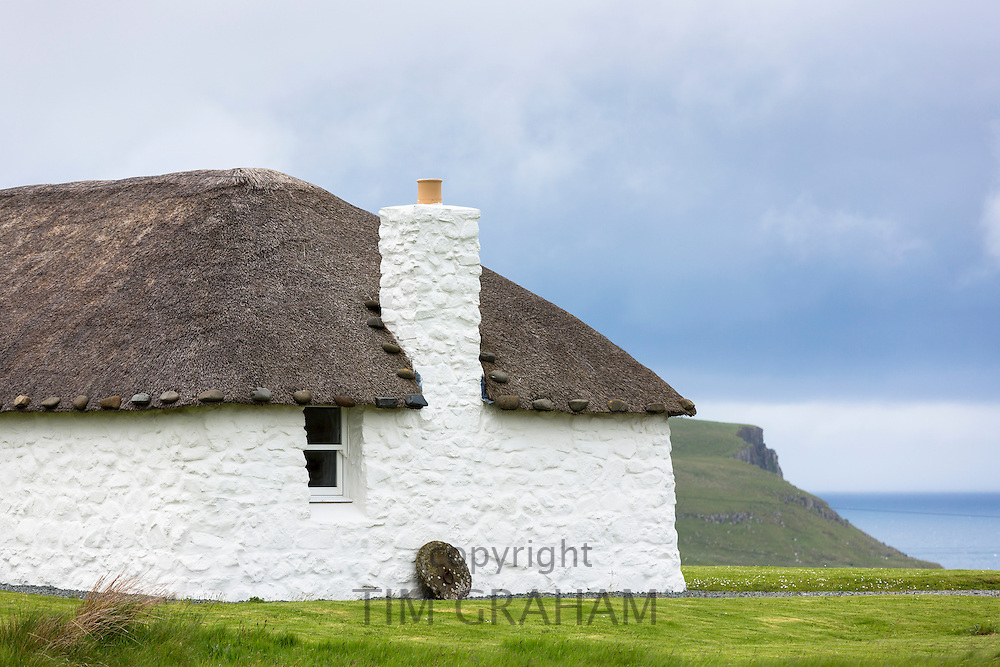 Thatched roof weighted with stones at restored thatched whitewashed barn cottage, Tigh Nighean Bhan, Isle of Skye, the Western Isles of Scotland, UK