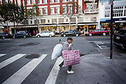 Een zwerver loopt met verzameld plastic door Polk Street in San Francisco. De Amerikaanse stad San Francisco aan de westkust is een van de grootste steden in Amerika en kenmerkt zich door de steile heuvels in de stad.<br /> <br /> A homeless woman walks with collected plastic garbage at Polk Street in San Francisco. The US city of San Francisco on the west coast is one of the largest cities in America and is characterized by the steep hills in the city.