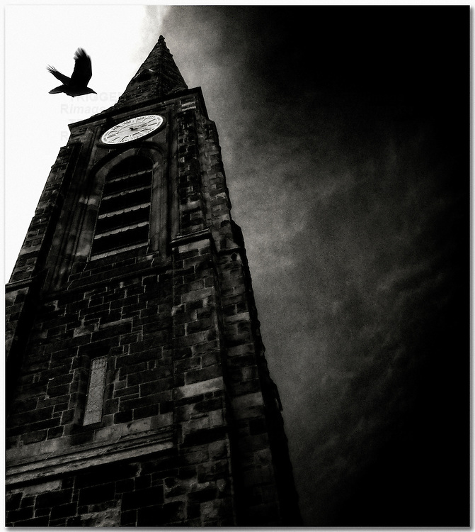 A bird flying by a tall dark bell tower with menacing sky