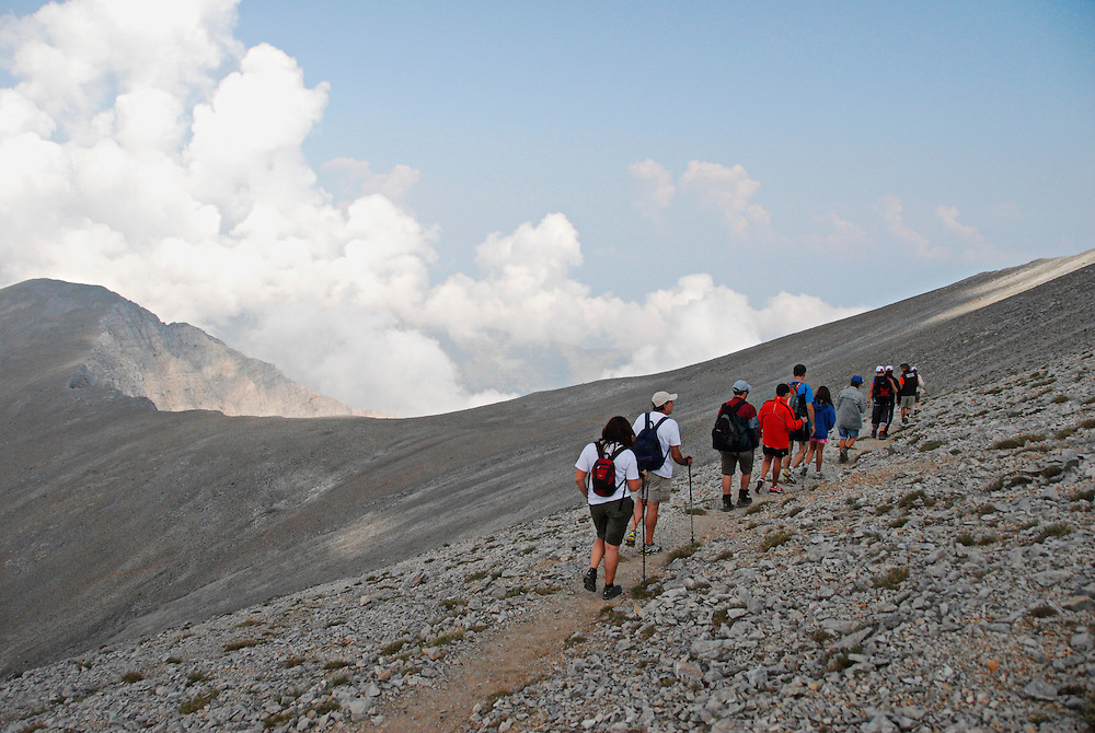 Climbers walking under the Skolio summit (2.912 m.), the second highest peak of mount Olympus, going towards Christakis refuge (2.500 m.) - a place reachable by car - part of the way of the E4 European long distance path, Kalyvia village, Elassona city, Thessaly region, central Greece.<br />