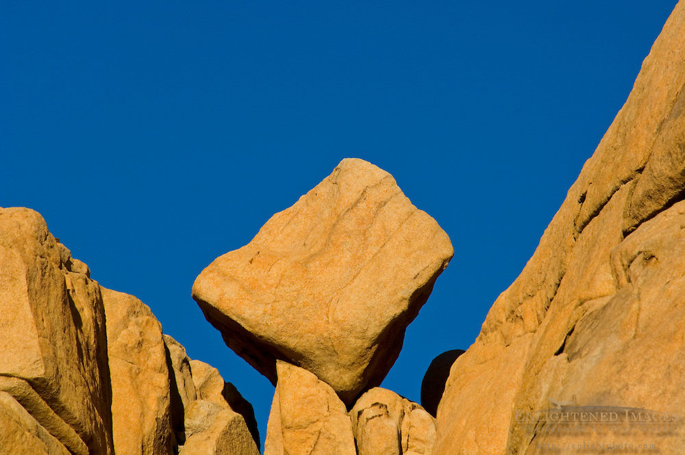 Eroded rock boulder balanced in wedge on outcrop near Barker Dam, Joshua Tree National Park, California