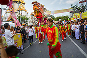 24 SEPTEMBER 2014 - BANGKOK, THAILAND: Chinese Dragon dancers perform on Yaowarat Road in Bangkok's Chinatown during the Vegetarian Festival Parade. The Vegetarian Festival is celebrated throughout Thailand. It is the Thai version of the The Nine Emperor Gods Festival, a nine-day Taoist celebration beginning on the eve of 9th lunar month of the Chinese calendar. During a period of nine days, those who are participating in the festival dress all in white and abstain from eating meat, poultry, seafood, and dairy products. Vendors and proprietors of restaurants indicate that vegetarian food is for sale by putting a yellow flag out with Thai characters for meatless written on it in red.    PHOTO BY JACK KURTZ