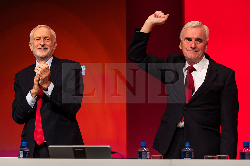 © Licensed to London News Pictures. 24/09/2018. Liverpool, UK. Shadow Chancellor John McDonnell MP (R) raises his fist after delivering his speech at the Labour Party Conference 2018, as Labour Party Leader Jeremy Corbyn MP (R) applauds. Photo credit: Rob Pinney/LNP