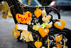 © Licensed to London News Pictures. 12/07/2017. LONDON, UK. A bench near Grenfell Tower, west London, is full of yellow knitted hearts while residents hold a vigil at the memorial wall on Wednesday 12 July, 2017, to remember those killed four weeks on from the tragedy when around 80 people are thought to have been killed. Photo credit: ISABEL INFANTES/LNP