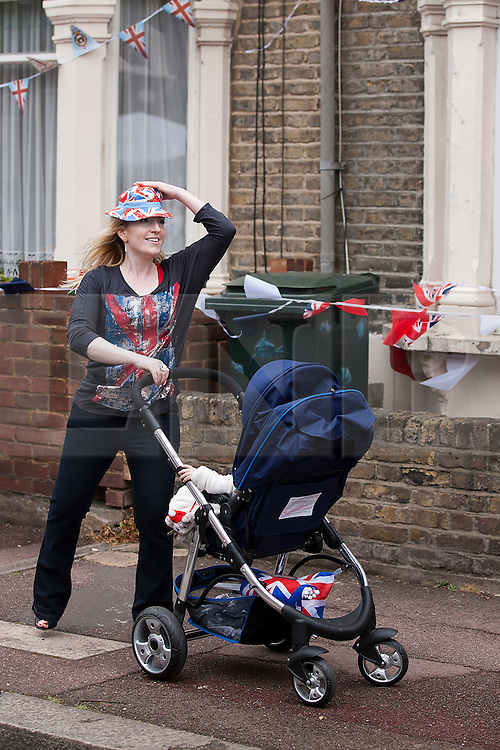 © Licensed to London News Pictures. 02/06/12. LONDON, UK. A mother pushes attempts to keep her Union Jack hat on during a windy Jubilee street party held by residents of Ravenscroft Road in Canning Town, East London. The Royal Jubilee celebrations. Great Britain is celebrating the 60th  anniversary of the country's Monarch HRH Queen Elizabeth II accession to the throne this weekend. Photo credit : LNP