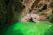 A kayaker departs Emerald Cave on the Colorado River.  When the season and time of day are right, light reflecting off of algae on the river bottom ignites the chamber in an impossibly green glow.