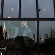 Ryan Saari, a pastor in Portland, Ore., is opening the region's first non-profit pub. True to the state's communitarian reputation, the Oregon Public House will be run by volunteers and all profits will go to charity. Here, he adjusts the lights.