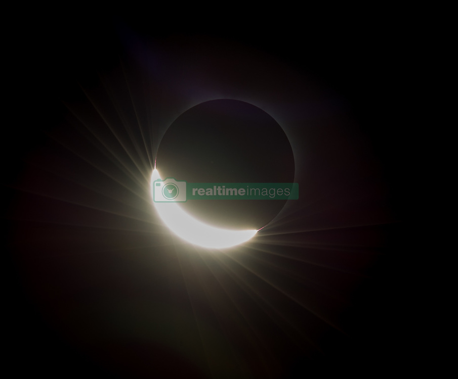 The last glimmer of the sun is seen as the moon makes its final move over the sun during the total solar eclipse on Monday, August 21, 2017 above Madras, Oregon. A total solar eclipse swept across a narrow portion of the contiguous United States from Lincoln Beach, Oregon to Charleston, South Carolina. A partial solar eclipse was visible across the entire North American continent along with parts of South America, Africa, and Europe.  Photo Credit: (NASA/Aubrey Gemignani)