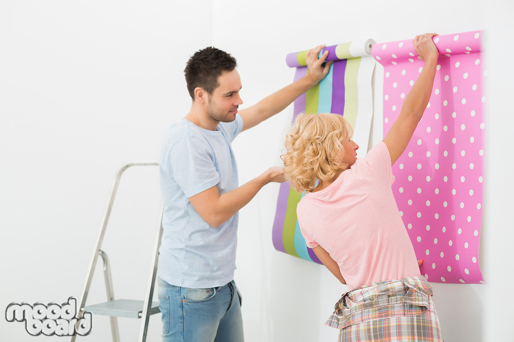 Couple holding up wallpaper samples in new house