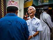 06 JULY 2016 - BANGKOK, THAILAND:  An elderly Muslim man greets a friend of his before Eid services at Ton Son Mosque in the Thonburi section of Bangkok. Eid al-Fitr is also called Feast of Breaking the Fast, the Sugar Feast, Bayram (Bajram), the Sweet Festival or Hari Raya Puasa and the Lesser Eid. It is an important Muslim religious holiday that marks the end of Ramadan, the Islamic holy month of fasting. Muslims are not allowed to fast on Eid. The holiday celebrates the conclusion of the 29 or 30 days of dawn-to-sunset fasting Muslims do during the month of Ramadan. Islam is the second largest religion in Thailand. Government sources say about 5% of Thais are Muslim, many in the Muslim community say the number is closer to 10%.       PHOTO BY JACK KURTZ