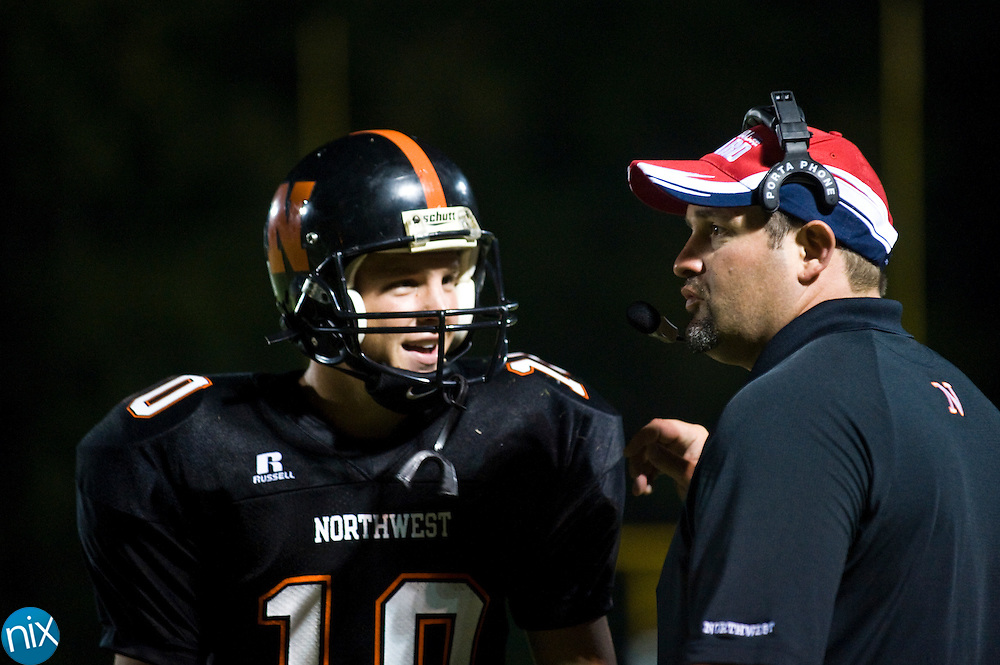 Northwest Cabarrus head coach Rich Williams talks with quarterback Colby Williford during a game against Parkwood Friday night in Concord. The Trojans won the non-conference matchup 42-0. (Photo by James Nix)
