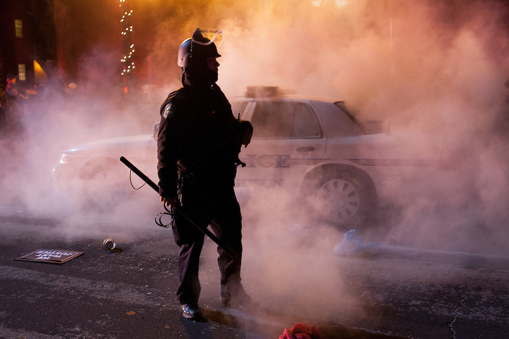 A policeman watches as a squad car, set on fire by protestors, burns in front of Ferguson City Hall. Demonstrators took to streets in response to a grand jury failing to indict officer Darren Wilson for the shooting death of Michael Brown Jr.