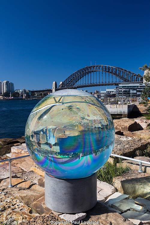 Sculpture at Barangaroo showing artwork titled Horizon by Lucy Humphrey. It uses the dramatic effect of sunlight to create a lens that transforms views upside down as seen with the harbour bridge.The art show falls at the same time  as Barangaroo Reserve celebrates its first birthday.