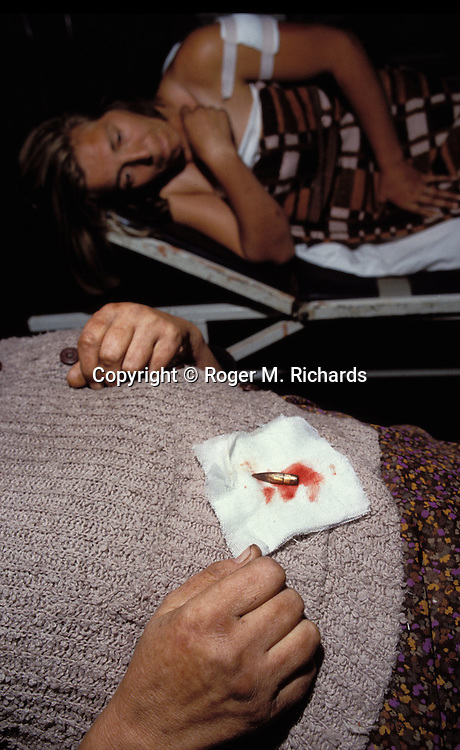 Two Bosnian women who were shot by a Serb sniper lie in the emergency room at Sarajevo's Kosevo Hospital, 1992. (Photo by Roger M. Richards)