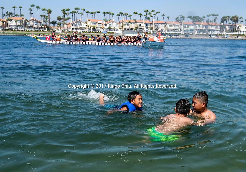 新华社照片,洛杉矶,2017年7月31日<br />     (国际)(7)第二十一届加州长滩龙舟节<br />     7月30日,小孩子在龙舟比赛场游泳。<br />     在美国洛杉矶长滩市海滨体育场举行的第二十一届年度长滩龙舟节,吸引百余队上千选手参赛。长滩龙舟节是加州最大的龙舟比赛,同时也展示了中国古代龙舟赛的运动。<br />     新华社发(赵汉荣摄)<br /> Children swim while dragon boat racers prepare to compete a 500-meter race at the 21st Annual Long Beach Dragon Boat Festival at Marine Stadium in Long Beach, California, the United States, on July 30, 2017. The Long Beach Dragon Boat Festival is held every year in July at Marine Stadium to hosting the largest dragon boat competitions in California. It showcases the ancient Chinese sport of dragon boat racing. (Xinhua/Zhao Hanrong)(Photo by Ringo Chiu)<br /> <br /> Usage Notes: This content is intended for editorial use only. For other uses, additional clearances may be required.