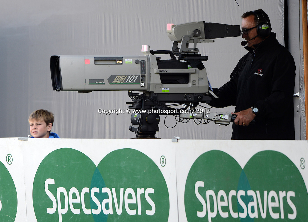 George Smith from Sky TV and a young fan on the sideline during the HRV Cup Twenty20 Cricket match between Auckland Aces and Canterbury Wizards at Eden Park on Friday 21 December 2012. Photo: Andrew Cornaga/Photosport.co.nz