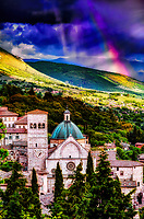 """""""The mystical rainbow of God above the Cathedral of San Rufino Assisi""""…<br /> <br /> This image is perhaps one of the most blessed and miraculous of my Italian journey. Upon arrival early that day in Assisi, I began taking photos the second I parked at Hotel Giotto just inside the walls in the foothills of Assisi. Perhaps Saint Francis arranged the dramatically perfect skies and coordinated every encounter. Beginning at the Basilica of Saint Francis, every second of the climb to the top of the mountain to the fortress Rocca Maggiore, a new surprise awaited around every corner. Upon my final steps to the top at almost sunset, the clouds parted and the low sun brightened as a slight mist of rain came down. Looking back over my shoulder, I was mesmerized at the appearance of this first of eventually two rainbows shining down behind the Duomo of Saint Rufino. I was able to capture a few horizontal and vertical images of the rainbows just as the sun began its descent below the horizon. My Italian journey was truly blessed by the hand of God."""