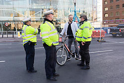 © Licensed to London News Pictures. 01/10/2016. LONDON, UK.  Police officers speak to a cyclist who has been cycling on the pavement on Tower Bridge. Tower Bridge closes to traffic today for three months for major renovations and repair. Pedestrians are still able to walk across the bridge. Photo credit: Vickie Flores/LNP