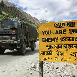 Indian army convoy passes military warning sign on the hazardous Kargil - Leh highway close to the 'Line of Control' (the de facto border) between India and Pakistan. Kashmir, India