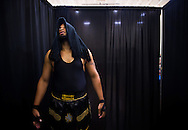 """Tyrannus prepares behind the curtain before making his entrance for a match at Championship Wrestling Entertainment's Live Pro Wrestling event Friday, May 15, 2015, at the Port St. Lucie Civic Center. CWE is a local """"indie"""" wrestling company headquartered in Port St. Lucie. (XAVIER MASCAREÑAS/TREASURE COAST NEWSPAPERS)"""