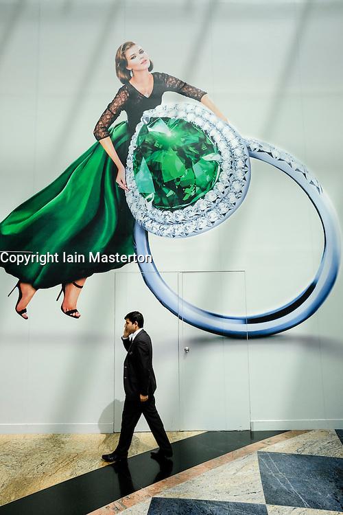 Man walks beneath billboard in Mall of the Emirates shopping centre in Dubai United Arab emirates