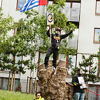 London, UK - 15 June 2012: a protester holds a West Papua flag while a man rests in Altab Ali Park during the Carnival of Dirt. More than 30 activist groups from London and around the world have come together to highlight the alleged illicit deeds of mining and extraction companies.