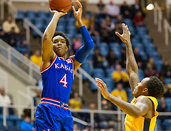 Jan 12, 2016; Morgantown, WV, USA; Kansas Jayhawks guard Devonte' Graham (4) shoots a three pointer over West Virginia Mountaineers guard Daxter Miles Jr. (4) during the first half at the WVU Coliseum. Mandatory Credit: Ben Queen-USA TODAY Sports