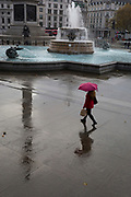 A lady walks through Trafalgar Square during a rain shower, on 12th November 2019, in London, England.