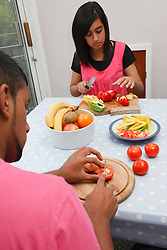 Teenage brother and sister cutting vegetables