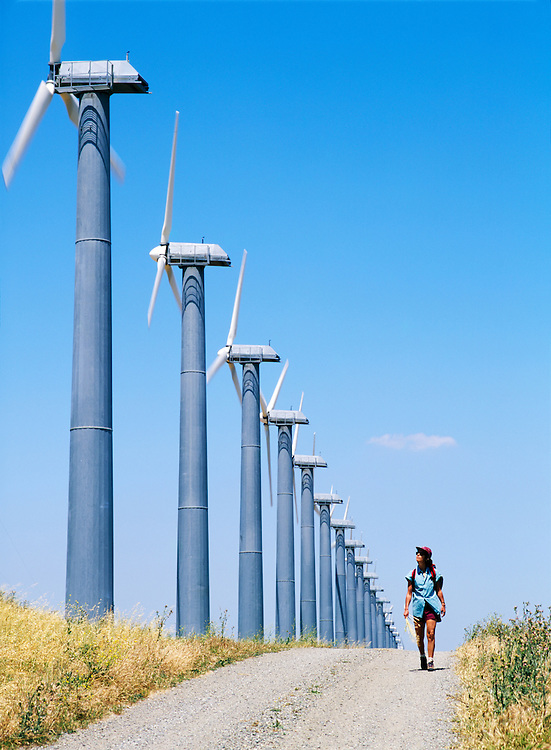 Woman walking on track beside wind turbines, part of the massive wind farm complex at Altamont near Livermore, California, USA.