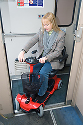 Woman steering electric mobility scooter into a train carriage,