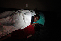 Children illuminated by their mother's flashlight sleep in a hotel lobby waiting out Hurricane Harvey in  Victoria, Texas August 26, 2017. REUTERS/Rick Wilking