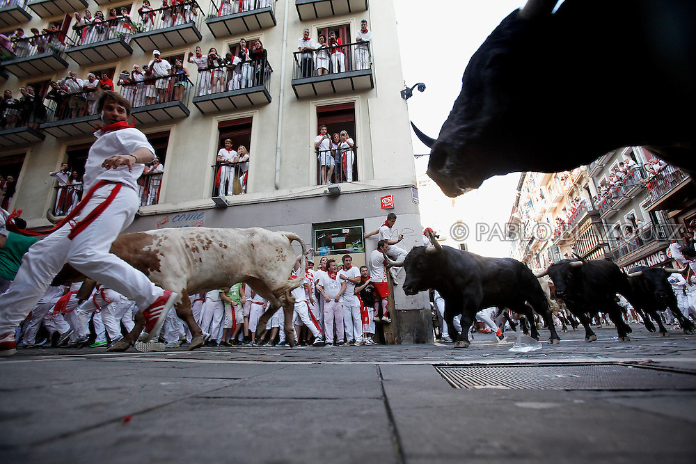 PAMPLONA, SPAIN - JULY 08: Revellers run with Dolores Aguirre's ranch fighting bulls at Curva Estafeta during the third day of the San Fermin Running Of The Bulls festival, on July 8, 2013 in Pamplona, Spain. The annual Fiesta de San Fermin, made famous by the 1926 novel of US writer Ernest Hemmingway 'The Sun Also Rises', involves the running of the bulls through the historic heart of Pamplona for nine days from July 6-14.  (© Pablo Blazquez)