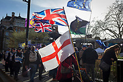 On the day that MPs in Parliament vote on a possible delay on Article 50 on EU Brexit negotiations by Prime Minister Theresa May, the British Union jack, the English Cros of St. George and the EU flag fly over College Green during a protest outside the House of Commons, on 14th March 2019, in Westminster, London, England.
