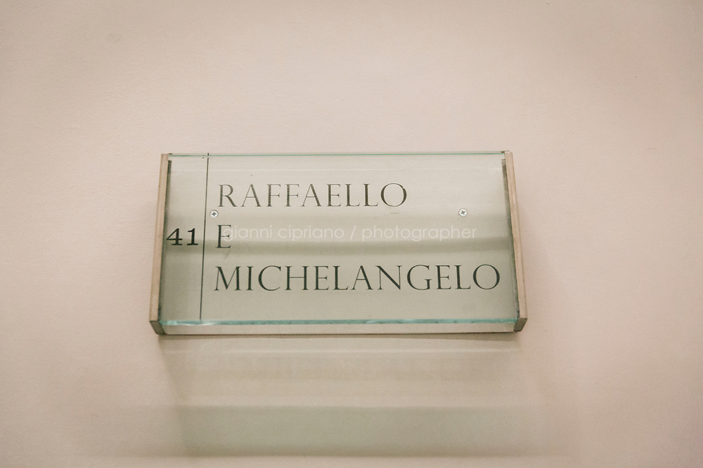 FLORENCE, ITALY - 3 JUNE 2018: The plaque of room 41 dedicated to Raphael and Michelangelo is seen here at the entrance of room 41 at the Uffizi, in Florence, Italy, on June 3rd 2018.<br /> <br /> As of Monday June 4th 2018, Room 41 or the &ldquo;Raphael and Michelangelo room&rdquo; of the Uffizi is part of the rearrangement of the museum's collection that has<br /> been defining Uffizi Director Eike Schmidt&rsquo;s grander vision for the Florentine museum.<br /> Next month, the museum&rsquo;s Leonardo three paintings will be installed in a<br /> nearby room. Together, these artists capture &ldquo;a magic moment in the<br /> first decade of the 16th century when Florence was the cultural and<br /> artistic center of the world,&rdquo; Mr. Schmidt said. Room 41 hosts, among other paintings, the dual portraits of Agnolo Doni and his wife Maddalena Strozzi painted by Raphael round 1504-1505, and the &ldquo;Holy Family&rdquo;, that Michelangelo painted for the Doni couple a year later, known as the<br /> Doni Tondo.