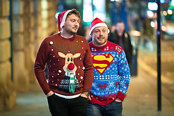"© Licensed to London News Pictures . 15/12/2017. Manchester, UK. Two men wearing Christmas jumpers and Santa hats on Market Street . Revellers out in Manchester City Centre overnight during "" Mad Friday "" , named for historically being one of the busiest nights of the year for the emergency services in the UK . Photo credit: Joel Goodman/LNP"
