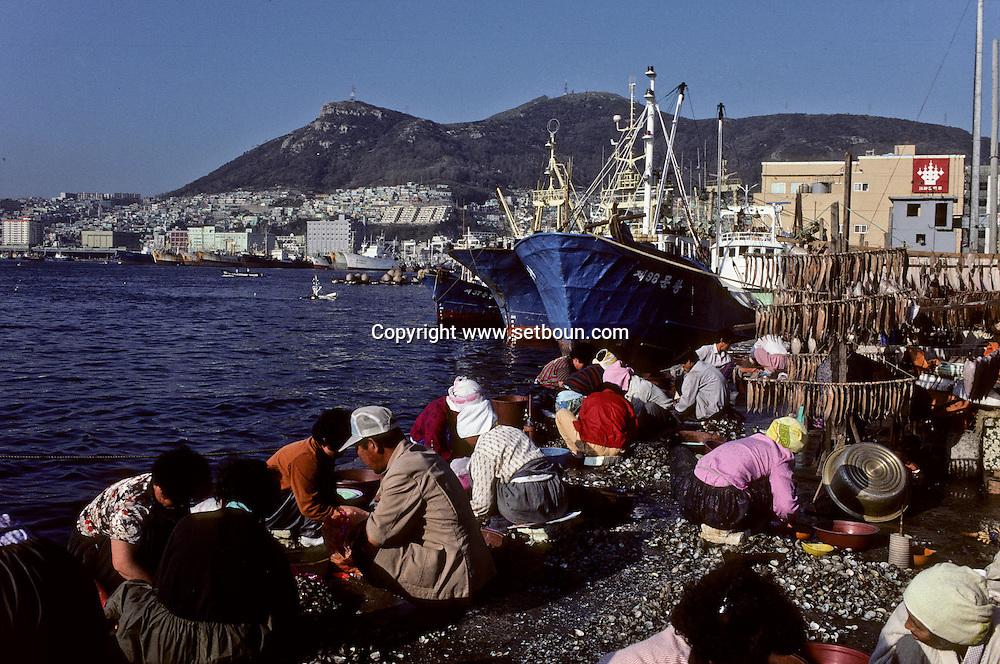 Pusan, South Korea --- Fishers Repairing Nets at Pusan Harbor +