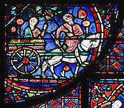 Julienne sits on a cart with the reliquary while the driver riding the horse turns to her. Evil spirits recognise the body as that of St Stephen but Julienne instructs the driver to say it is the body of her husband. Section of transporting the body on a cart, 1220-25, from the Life of St Stephen and transferral of his relics window in the ambulatory of Chartres Cathedral, Eure-et-Loir, France. This window, unusually dominantly red in colour, tells the story of the life of St Stephen, the first Christian martyr, who died c. 36 AD and whose relics are held at Chartres. It is situated in the chapel dedicated to martyrs. Chartres cathedral was built 1194-1250 and is a fine example of Gothic architecture. Most of its windows date from 1205-40 although a few earlier 12th century examples are also intact. It was declared a UNESCO World Heritage Site in 1979. Picture by Manuel Cohen