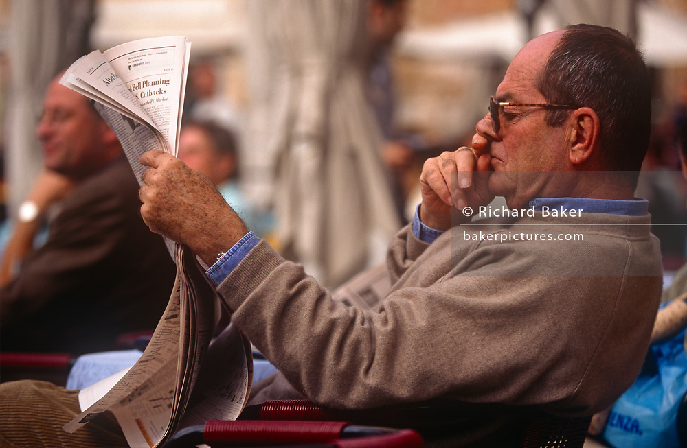 A cafe customer reads his copy of the English language Herald Tribune newspaper in the Italian capital, on 3rd November 1999, in Rome, Italy.