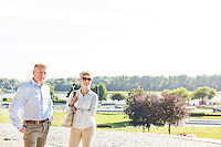 Confident middle-aged couple standing at park against clear sky