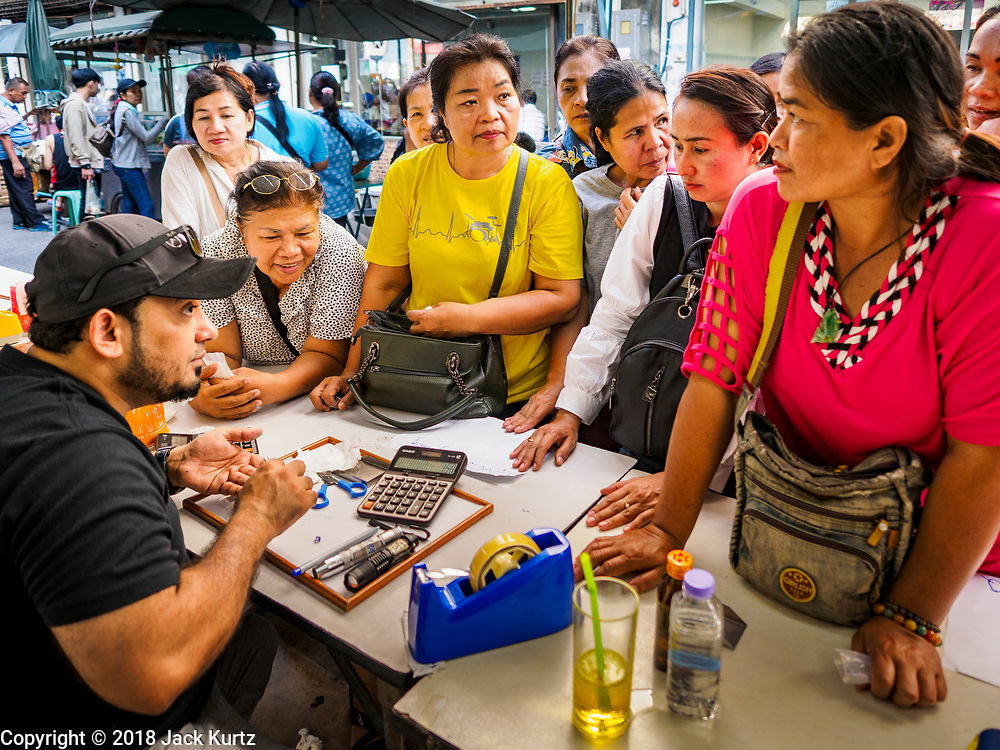 21 DECEMBER 2018 - CHANTABURI, THAILAND: Thai women talk to an Indian gem merchant in the gem market in Chantaburi. The gem market in Chantaburi, a provincial town in eastern Thailand, is open on weekends. Chantaburi used to be an active gem mining area in Thailand, but the mines are played out now. Now buyers and sellers come from around the world to Chantaburi for the weekend market. Many of the stones come from Myanmar, others come from mines in Afghanistan and Africa.       PHOTO BY JACK KURTZ