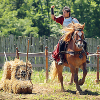 Terral Hill, portraying Sir Leon from Scotland, celebrated after his spear hit its mark on a bale of straw as he participated in the jousting competition at the Highland Renaissance Festival in Eminence, Ky., on 6/19/10. The jousting tournament was performed by the Cavalo Equestrian Arts troupe out of Florida. Photo by David Stephenson