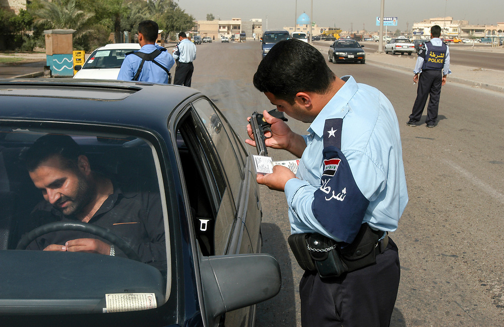 An Iraqi Policeman checks the permit of a man carring a fire arm in his car at a check point in the al-Bahya area of Baghdad.<br /> Baghdad, Iraq. 28/04/2004