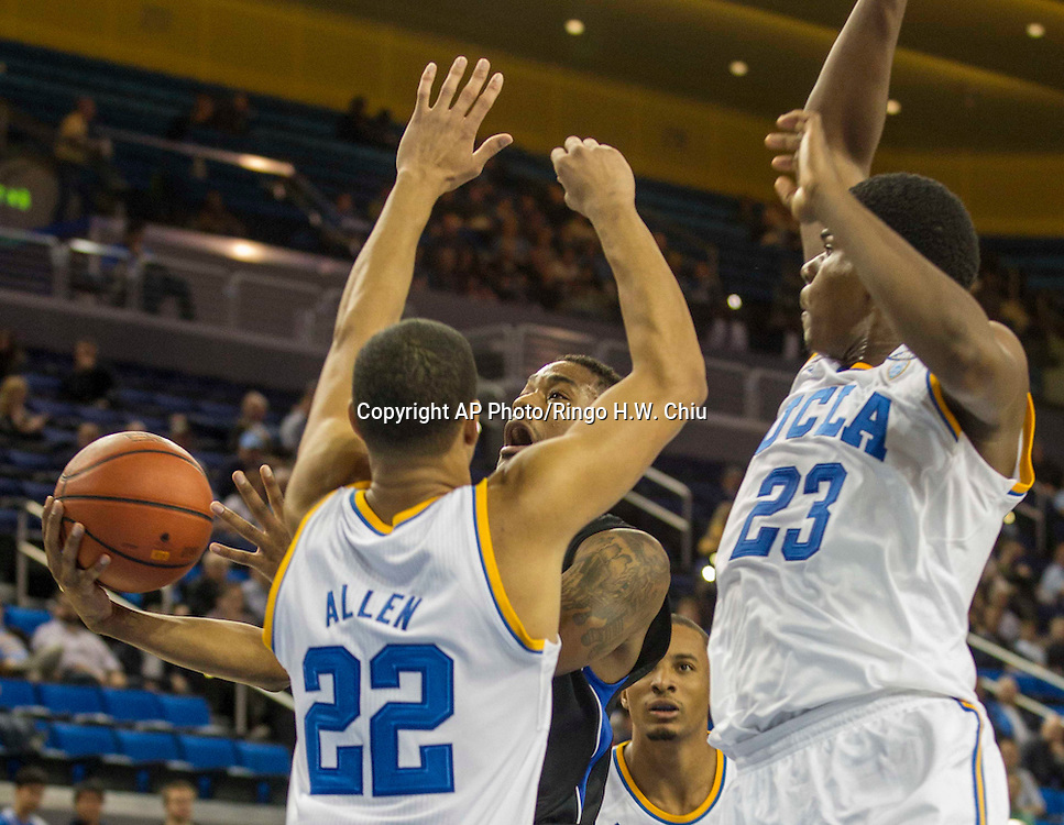 Cal State San Bernardino's Donte Medder #5 goes up against UCLA's Noah Allen #22 and Evan Jenkins #23 in the first half of their basketball game at UCLA's Pauley Pavilion during an NCAA college exhibition basketball game, Wednesday, Oct. 30, 2013 in Los Angeles. (AP Photo/Ringo H.W. Chiu)