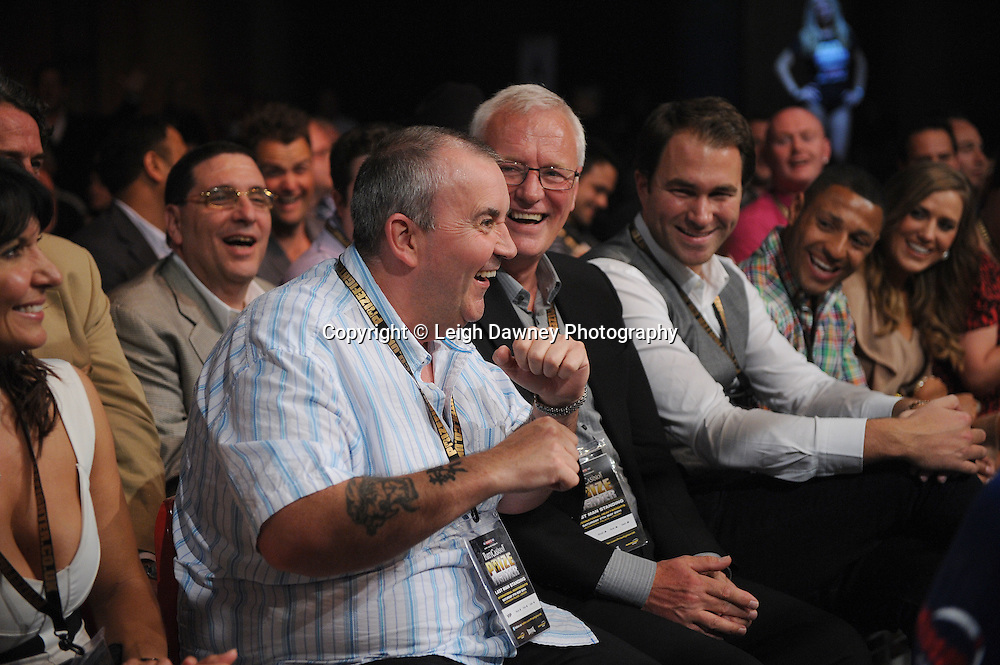 Phil Taylor ringside having a joke with the crowd and seated next to promoters Barry & Eddie Hearn at Prizefighter International on Saturday 7th May 2011. Prizefighter / Matchroom. Photo credit © Leigh Dawney. Alexandra Palace, London.