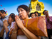 18 NOVEMBER 2015 - BANGKOK, THAILAND:  A woman holding monk's robes she donated to make merit prays at the chedi at the top of Wat Saket during the parade marking the start of the temple's annual fair. Wat Saket is on a man-made hill in the historic section of Bangkok. The temple has golden spire that is 260 feet high which was the highest point in Bangkok for more than 100 years. The temple construction began in the 1800s in the reign of King Rama III and was completed in the reign of King Rama IV. The annual temple fair is held on the 12th lunar month, for nine days around the November full moon. During the fair a red cloth (reminiscent of a monk's robe) is placed around the Golden Mount while the temple grounds hosts Thai traditional theatre, food stalls and traditional shows.     PHOTO BY JACK KURTZ