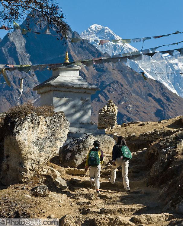"School children walk towards Khumjung, in Sagarmatha National Park, Nepal, beneath Mount Everest (29,035 feet / 8850 meters elevation above sea level), the highest mountain on Earth. Mount Everest was first called Chomolungma or Qomolangma (""Goddess Mother of the Earth"" in Tibetan). In 1865, Andrew Waugh, the British surveyor-general of India named the mountain for his chief and predecessor, Colonel Sir George Everest. In the 1960s, the Government of Nepal named the mountain Sagarmatha, meaning ""Goddess of the Sky"". The mountain, which is part of the Himalaya range in High Asia, is located on the border between Nepal and Tibet, China. Sagarmatha National Park was created in 1976 and honored as a UNESCO World Heritage Site in 1979."