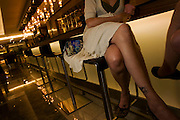 A young lady from sits on a stool at a hotel bar with a friend at the Sphere Bar at Heathow Airport