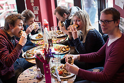 © licensed to London News Pictures. London, UK 15/03/2013. A group of people eating 100% horse meat burgers at The Lord Nelson pub in Southwark, London as the pub starts to serve 100% horsemeat burgers to their customers. (Clockwise names: Chris Watkins, Ewan Barker, Hamilton Ross, Bea Beazley, Tadgh Jordan) Photo credit: Tolga Akmen/LNP